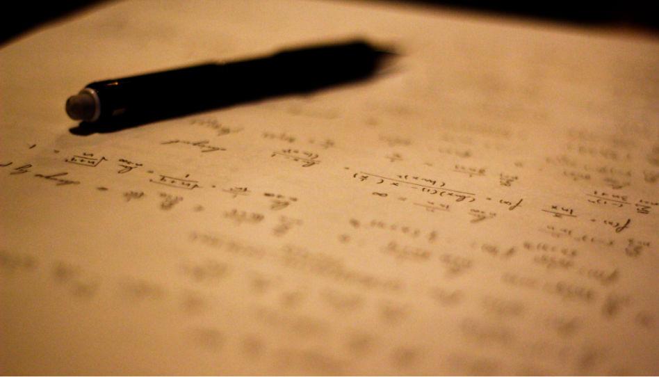 Zu sehen ist ein Stift, liegend auf einem Zettel mit Mathematikaufgaben.