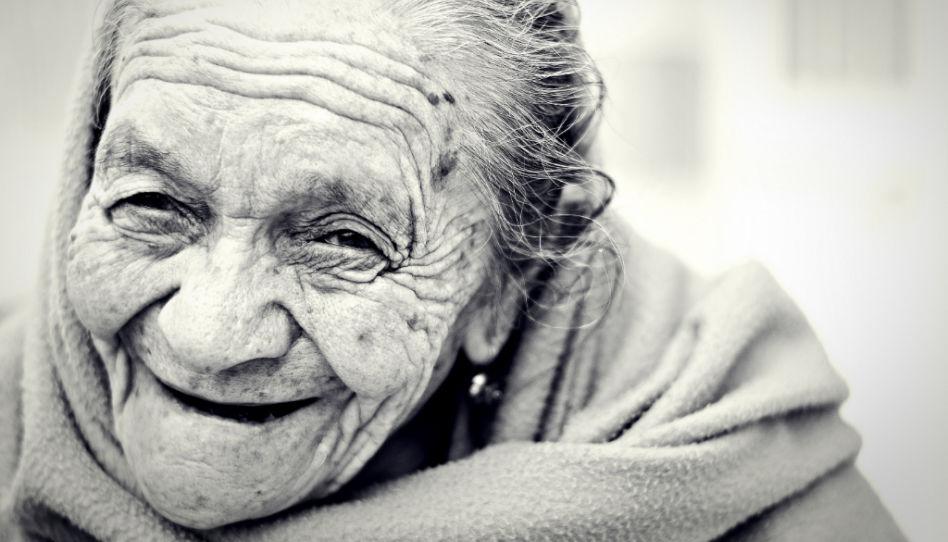 Zu sehen ist eine alte lächelnde Frau auf einem Schwarz-Weiß-Foto.