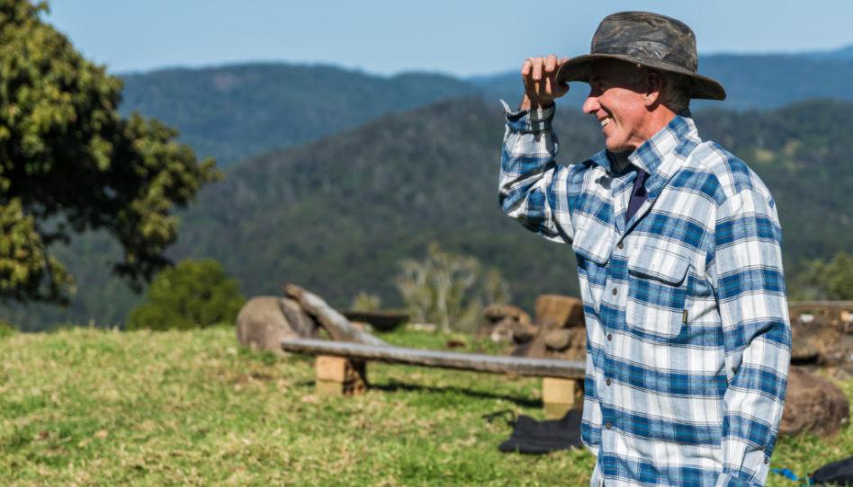 Hier zu sehen ist ein strahlender Man mit Hut und kariertem Hemd, der sich irgendwo in den Bergen befindet.