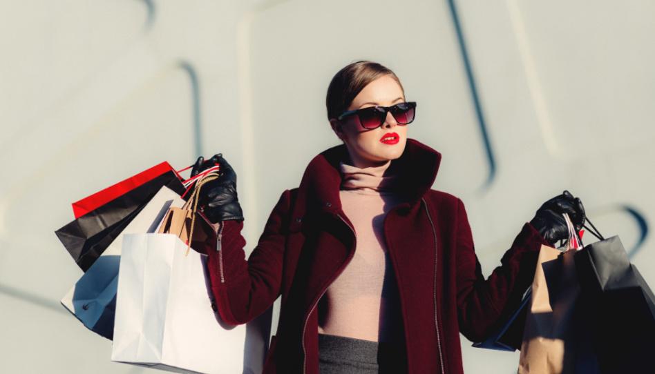 Der Minimalismus möchte der Konsumgesellschaft entgegenwirken. Hier ist eine Frau mit Sonnenbrille zu sehen, die in beiden Händen zig Einkaufstaschen hält.