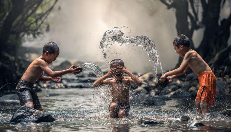 Beim Minimalismus geht es im Kern darum, ein glücklicheres Leben zu führen. Auf diesem Foto sind daher drei Kinder zu sehen, die glücklich im Wasser spielen.