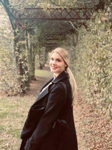 Dies ist ein weiteres privates Foto von Leslie. Sie steht in einem Park und dreht sich lächelnd zur Kamera.