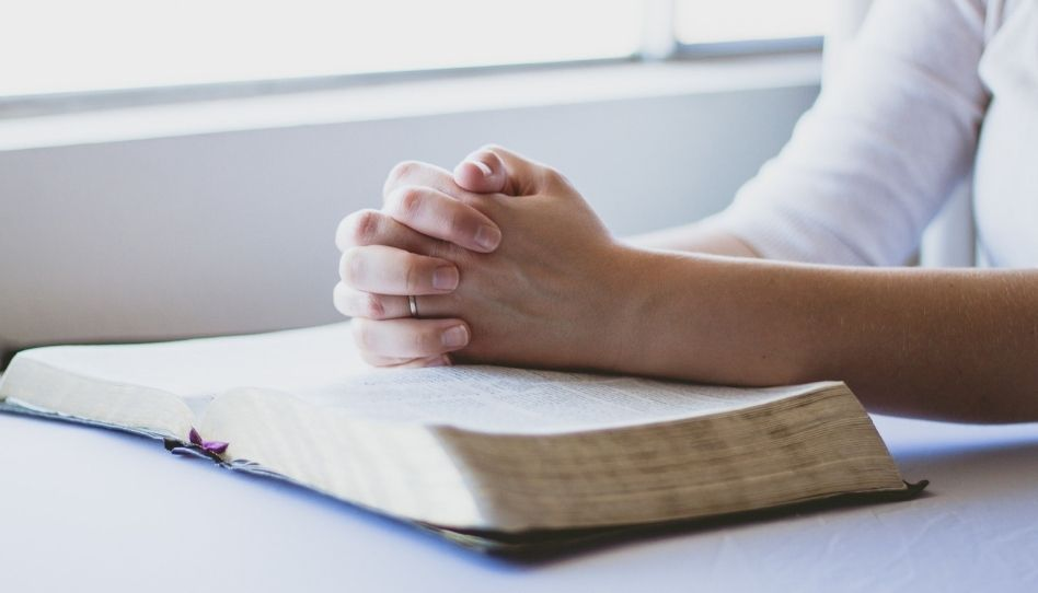 Zu sehen sind zum Beten gefaltete Hände, die auf einer Bibel liegen.