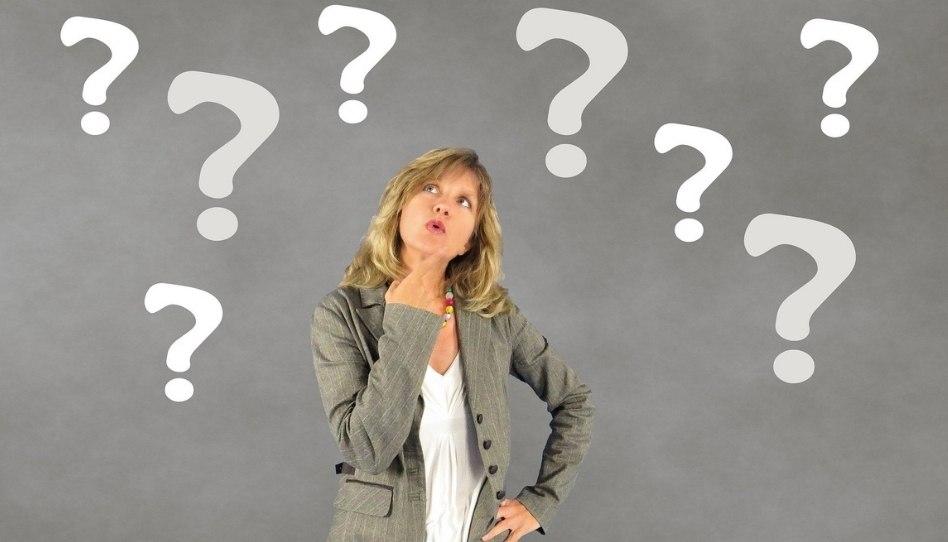 Das Bild einer nachdenklichen Frau mit Fragezeichen um sie herum