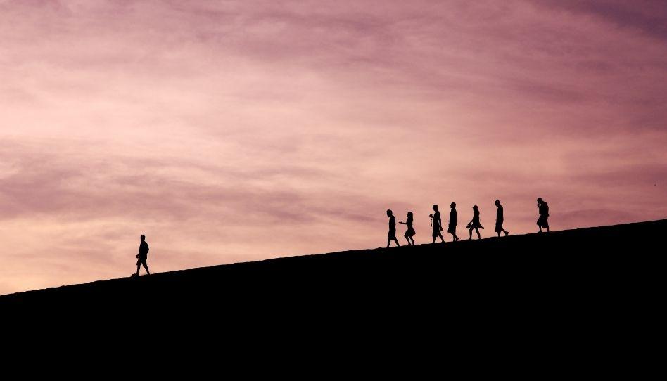 Mehrere Personen gehen einen Abhang hinunter. Eine Person geht voraus, während die anderen, mit etwas Abstand, in einer Gruppe folgen.
